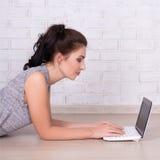 Concepto de Internet - mujer hermosa que miente en el piso y usar Foto de archivo libre de regalías