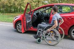 Concepto de la accesibilidad Hombre perjudicado o discapacitado en la silla de ruedas cerca del coche fotografía de archivo libre de regalías