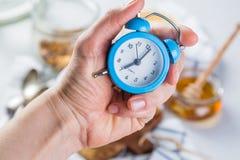 Concepto de la alarma de la mañana - mano con el reloj Imagenes de archivo