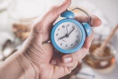 Concepto de la alarma de la mañana - mano con el reloj Fotografía de archivo