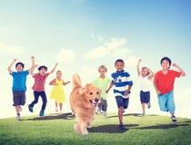 Concepto de la amistad del perro casero del verano de la diversión de los niños de los niños Imagen de archivo