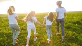 Concepto de la amistad Mujeres felices jovenes con sus hijas que corren a través del campo en la puesta del sol metrajes