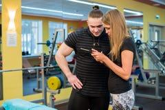 Concepto de la aptitud, del deporte, del ejercicio, de la tecnología y de la dieta - mujer joven sonriente e instructor personal  foto de archivo