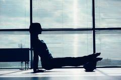 Concepto de la aptitud, del deporte, del entrenamiento y de la forma de vida - mujer que hace pilates en el piso con el contorno  Fotografía de archivo