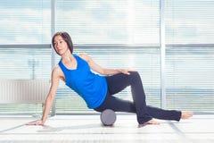 Concepto de la aptitud, del deporte, del entrenamiento y de la forma de vida - mujer que hace pilates en el piso con el rodillo d Foto de archivo libre de regalías