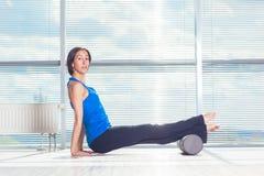 Concepto de la aptitud, del deporte, del entrenamiento y de la forma de vida - mujer que hace pilates en el piso con el rodillo d Imágenes de archivo libres de regalías