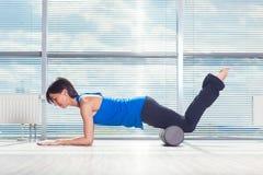Concepto de la aptitud, del deporte, del entrenamiento y de la forma de vida - mujer que hace pilates en el piso con el rodillo d Imagenes de archivo