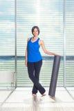 Concepto de la aptitud, del deporte, del entrenamiento y de la forma de vida - mujer que hace pilates en el piso con el rodillo d Fotos de archivo libres de regalías