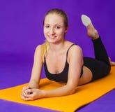 Concepto de la aptitud, del deporte, del entrenamiento y de la forma de vida - mujer sonriente que hace ejercicios en la estera e Imagen de archivo