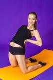 Concepto de la aptitud, del deporte, del entrenamiento y de la forma de vida - mujer sonriente que hace ejercicios en la estera e Fotografía de archivo