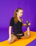 Concepto de la aptitud, del deporte, del entrenamiento y de la forma de vida - mujer sonriente que hace ejercicios en la estera e Foto de archivo libre de regalías