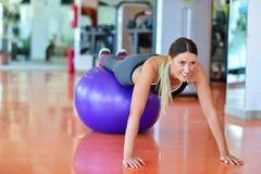 Concepto de la aptitud, del hogar y de la dieta - muchacha sonriente que ejercita con la bola de la aptitud en el gimnasio Imagenes de archivo