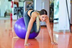 Concepto de la aptitud, del hogar y de la dieta - muchacha sonriente que ejercita con la bola de la aptitud en el gimnasio Imágenes de archivo libres de regalías