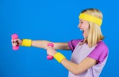 Concepto de la aptitud muchacha que ejercita con pesa de gimnasia Instructor de la aptitud llevar a cabo poco fondo azul de la pe fotos de archivo libres de regalías