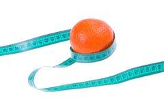 Concepto de la aptitud: Naranja con una ruleta (aislada) Imagenes de archivo