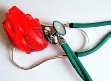 Concepto de la atención sanitaria - estetoscopio verde con el corazón rojo Imágenes de archivo libres de regalías