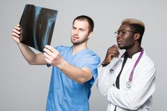 Concepto de la atención sanitaria, médico y de la radiología - dos doctores que miran la radiografía en fondo gris imágenes de archivo libres de regalías