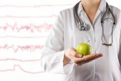 Concepto de la atención sanitaria y de la medicina - la mano del doctor de sexo femenino que sostiene la manzana verde Ciérrese e Imagen de archivo libre de regalías