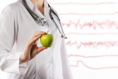 Concepto de la atención sanitaria y de la medicina - la mano del doctor de sexo femenino que sostiene la manzana verde Ciérrese e Fotografía de archivo