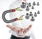 Concepto de la atracción del cliente que eleva y mantiene flotando sobre una mano imagen de archivo