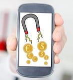 Concepto de la atracción del dinero en un smartphone Imágenes de archivo libres de regalías