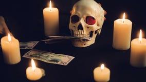 Concepto de la avaricia del dinero con el cráneo humano metrajes