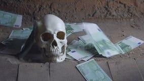 Concepto de la avaricia del dinero con el cráneo humano, el cráneo y el dinero que cae almacen de video