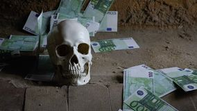 Concepto de la avaricia del dinero con el cráneo humano, el cráneo y el dinero que cae almacen de metraje de vídeo