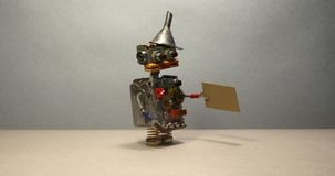 Concepto de la búsqueda de trabajo El robot quiere conseguir un trabajo Robot parado divertido del juguete que camina con una mue almacen de metraje de vídeo