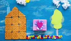 Concepto de la bandera de una casa de la galleta en una trayectoria de madera de la familia del fondo de la nube del cielo azul fotos de archivo