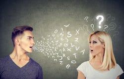 Concepto de la barrera linguística Hombre hermoso que habla con una mujer atractiva con el signo de interrogación imagenes de archivo