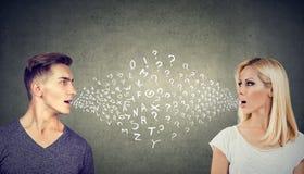 Concepto de la barrera linguística Hombre hermoso que habla con una mujer atractiva con muchas preguntas foto de archivo