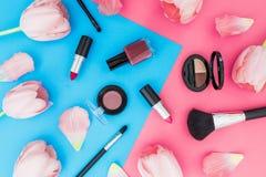 Concepto de la belleza con las flores y los cosméticos de los tulipanes en fondo azul y rosado Visión superior fotos de archivo libres de regalías