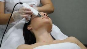 Concepto de la belleza Procedimiento del cosmético de la cara Especialista de la belleza que hace la peladura ultrasónica para la metrajes