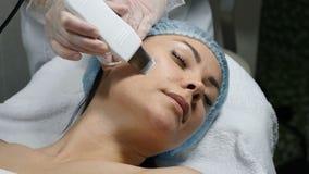 Concepto de la belleza Procedimiento del cosmético de la cara Especialista de la belleza que hace la peladura ultrasónica para la almacen de video