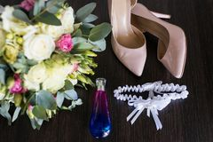 Concepto de la boda Accesorios de la boda Zapatos, botella de perfume beige nupciales, casandose la liga y el ramo del lujo Foto de archivo libre de regalías