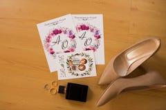 Concepto de la boda Accesorios de la boda Zapatos nupciales, botella de perfume, anillos de bodas e invitaciones de lujo Fotos de archivo