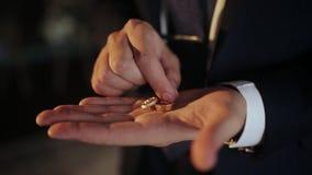 Concepto de la boda - prepare los anillos de bodas de oro de los controles en la palma de la mano metrajes
