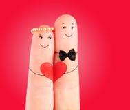 Concepto de la boda, recienes casados con el corazón contra fondo rojo imágenes de archivo libres de regalías