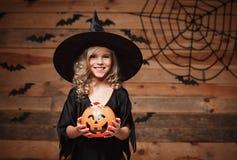 Concepto de la bruja de Halloween - el pequeño niño caucásico de la bruja goza con el tarro de la calabaza del caramelo de Hallow Imágenes de archivo libres de regalías