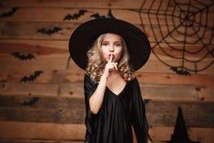 Concepto de la bruja de Halloween - el primer tiró del pequeño niño caucásico de la bruja que sostenía el dedo índice en los labi imagenes de archivo