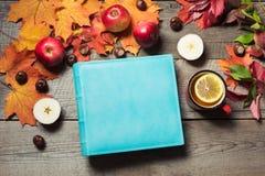 Concepto de la caída Álbum azul con el espacio para el texto y la taza del té, decoración de las hojas de otoño, manzanas en el t Fotografía de archivo