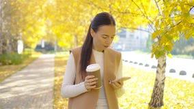 Concepto de la caída - café de consumición de la mujer hermosa en parque del otoño debajo del follaje de otoño metrajes