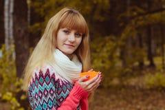 Concepto de la caída - café de consumición de la mujer del otoño en parque Fotografía de archivo libre de regalías
