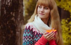 Concepto de la caída - café de consumición de la mujer del otoño en parque Foto de archivo