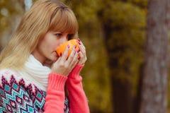 Concepto de la caída - café de consumición de la mujer del otoño en parque Imagen de archivo