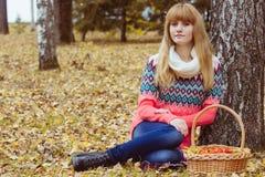Concepto de la caída - mujer del otoño que se sienta en parque Foto de archivo