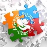 Concepto de la caridad en rompecabezas multicolor. Imagenes de archivo