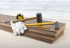 Concepto de la carpintería Diversos herramientas y guantes en el nuevo suelo laminado Copie el espacio para el texto imagen de archivo libre de regalías