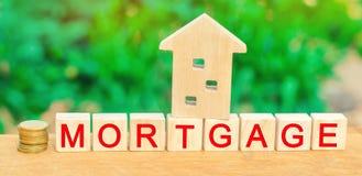 Concepto de la casa miniatura de la casa y de Money Bloques de madera y el ` de la hipoteca del ` de la inscripción crédito para  fotos de archivo